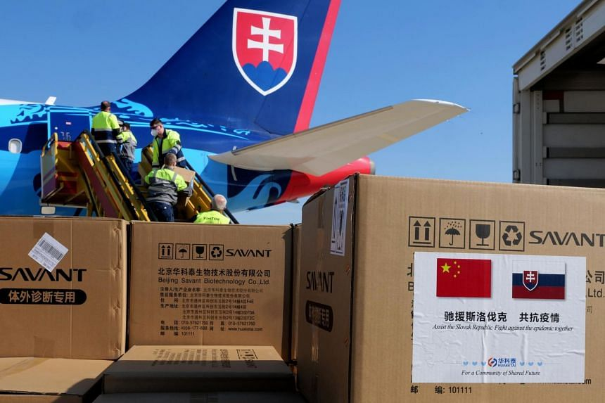 Slovak police officers unload a plane from from Beijing loaded with one hundred thousand test kits and one million face masks at M.R. Stefanilk airport in Bratislava, Slovakia, on March 19, 2020.