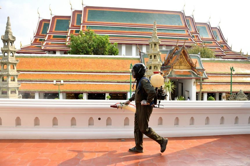 A health worker sprays disinfectant due to the outbreak of coronavirus, at inside Wat Suthat Thepwararam temple in Bangkok, Thailand, on March 17, 2020.