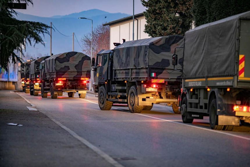 Italian military trucks drive through streets of Bergamo after the army were deployed to move coffins from the town to neighbouring provinces after funeral services were overwhelmed, in Bergamo, Italy, on March 18, 2020.