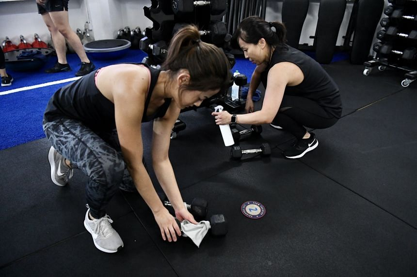 Patrons at F45 Holland Village sanitising equipment between sets. At least 10 local gyms have issued notices via e-mail or social media informing members of current and updated hygiene measures at their respective premises and urging members to pract