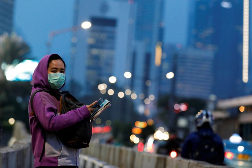 A woman wearing a protective face mask stands on the sidewalk amid the coronavirus outbreak in Jakarta, Indonesia, on March 19, 2020.