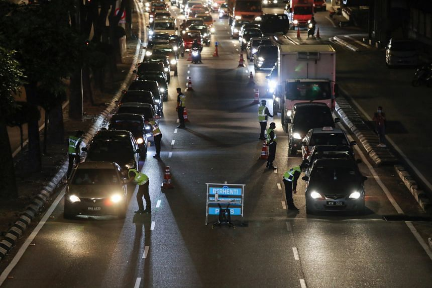 Police officers check vehicles at a roadblock to enforce movement control order due to the spread of the coronavirus disease in Kuala Lumpur, on March 19, 2020.