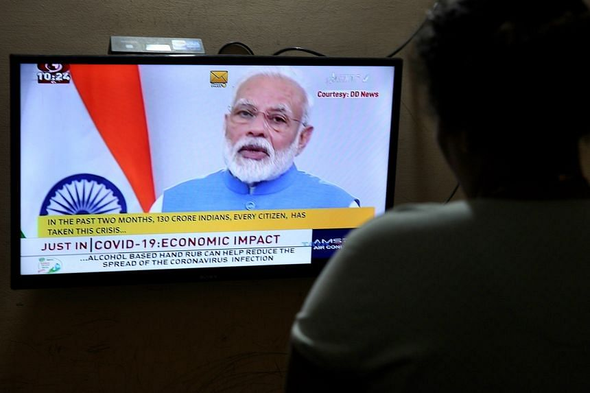 An Indian watches a live broadcast of Prime Minister Narendra Modi's address to the nation, in Bangalore, India, on March 19, 2020.