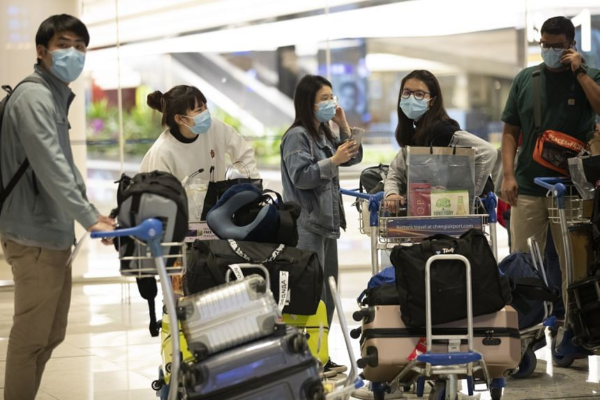 Travellers are seen with their luggage at the arrival hall of Changi Airport Terminal 1 in Singapore, on March 19, 2020.