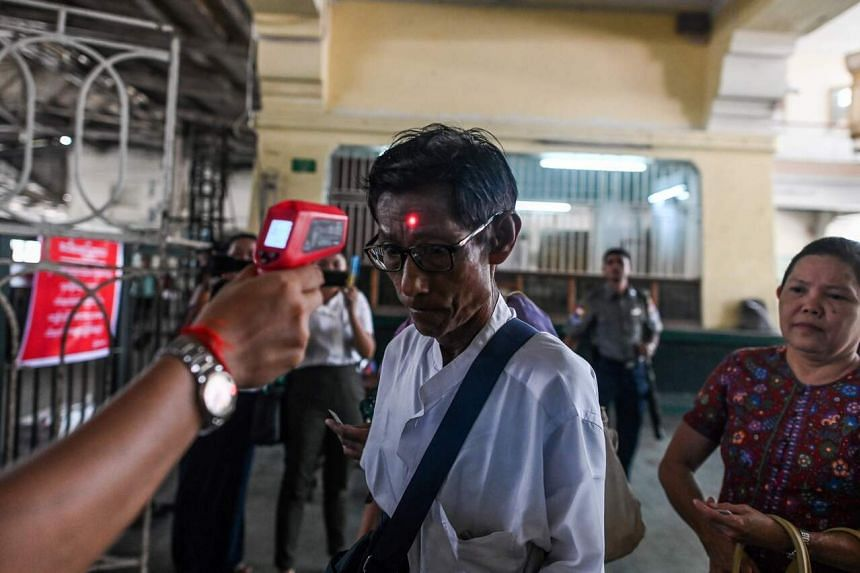 A passenger's temperature being taken as a preventive measure against Covid-19, the disease caused by the new coronavirus, at the central railway station in Yangon on March 19, 2020.