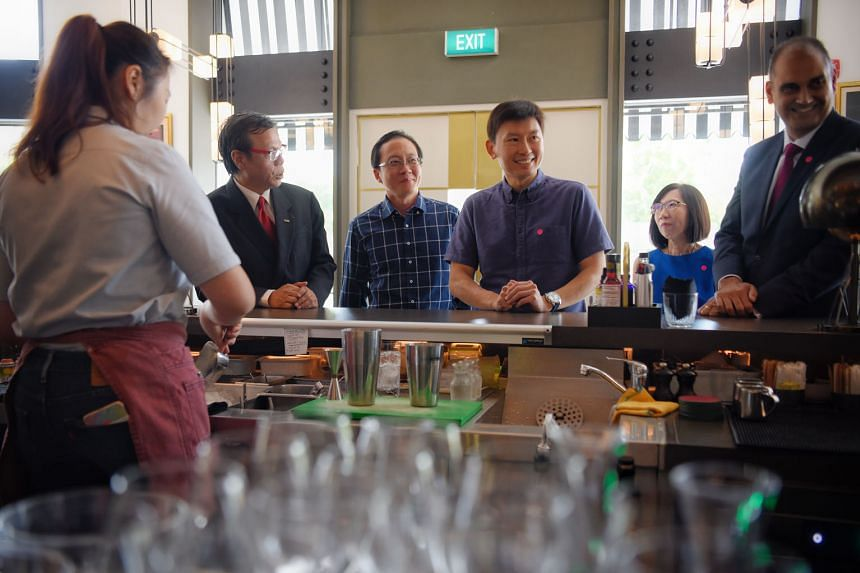 Mr Chee Hong Tat, Senior Minister of State for Trade and Industry as well as Education (centre), observing Fairmont Singapore hotel employee Isabella Lim, 29, concocting a cocktail at Prego restaurant yesterday.