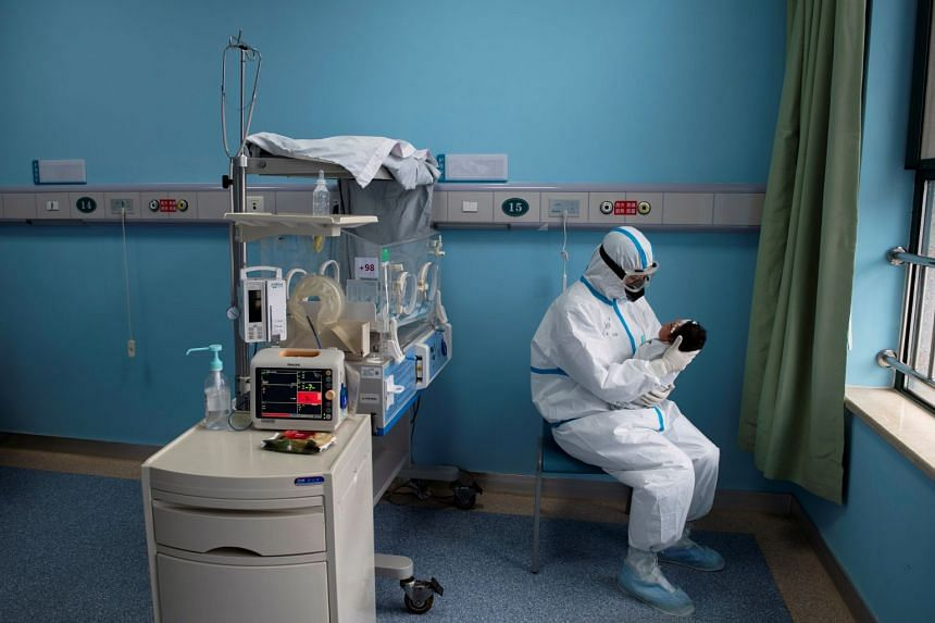 A nurse in a protective suit attends to a baby with Covid-19 in an isolation ward at Wuhan Children's Hospital, March 16, 2020.