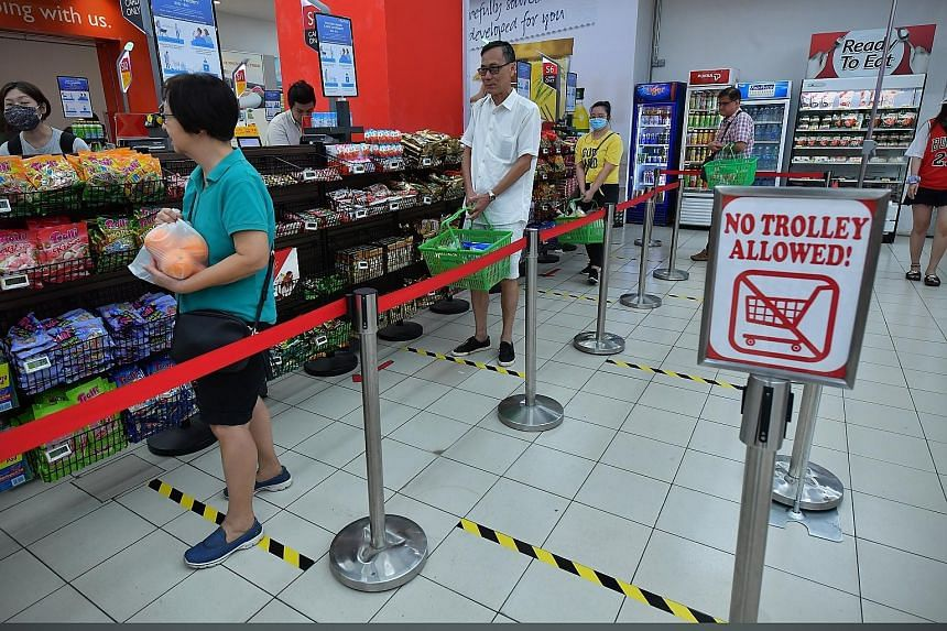 Shoppers at FairPrice in Nex queueing a metre apart by following floor markers. Safe distancing will also be the norm at other public areas such as entertainment venues, restaurants, hawker centres and cinemas. ST PHOTO: NG SOR LUAN