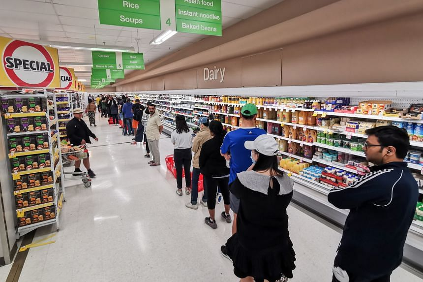 People queue for a delivery of toilet paper, paper towel and pasta at a Coles supermarket in Sydney, Australia, on March 20, 2020.