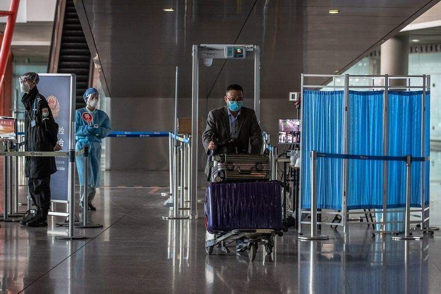 A man wearing a protective face mask walks with his luggage through the security check at the Capital International Airport in Beijing on March 17, 2020.