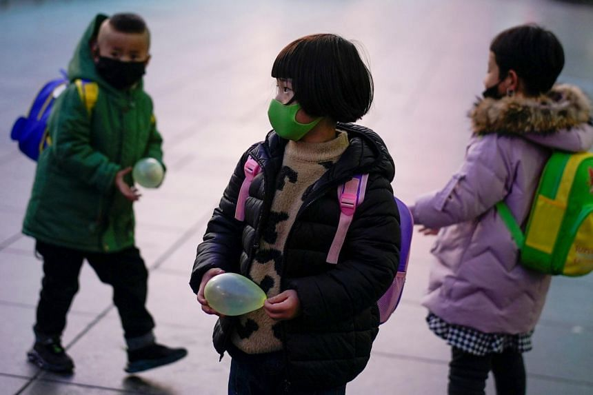 Children wearing face masks seen at a railway station in Shanghai on March 5, 2020.