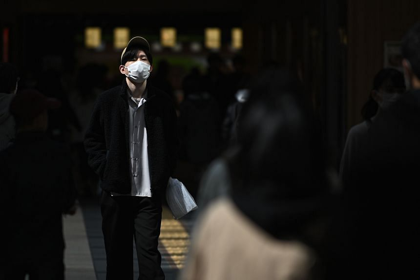 A man wearing a face mask walks in Sendai railway station on March 21, 2020.