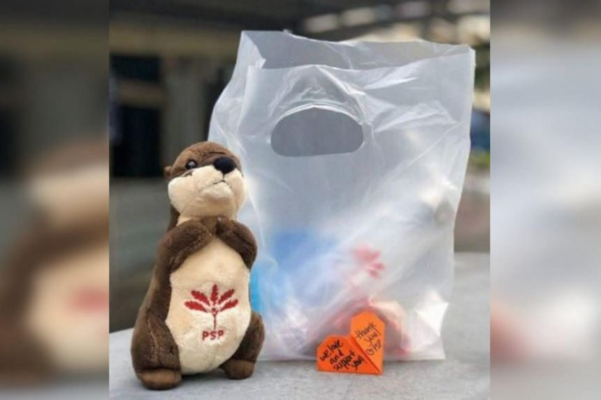 Above: Progress Singapore Party's goodie bag for healthcare workers containing biscuits, a water bottle and an isotonic drink (toy otter not included).