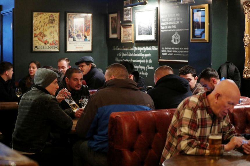 People in a pub after Britain's Prime Minister Boris Johnson announced that cafes, pubs and restaurants across the country to close in London on March 20, 2020.