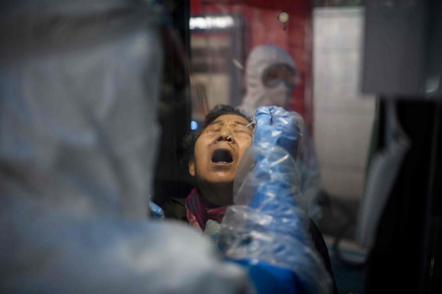 A woman receives a coronavirus test swab at a testing booth outside the Yangji hospital in Seoul on March 17, 2020.