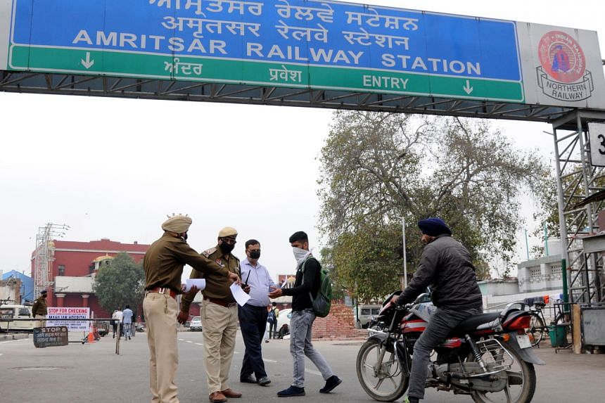 Punjab police officers distribute coronavirus awareness pamphlets outside a railway station in Amritsar, India, on March 21, 2020.