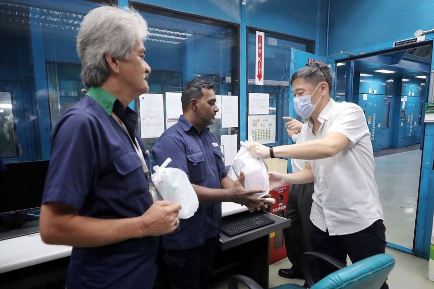 Singapore Press Holdings' (SPH) deputy chief executive Anthony Tan (right) distributing care packages to Malaysian staff at SPH's  print centre on March 21, 2020.