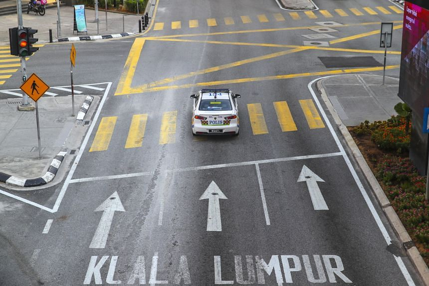 A police car patrols a street in Kuala Lumpur on March 20, the third day of Movement Control Order enforcement in Malaysia.