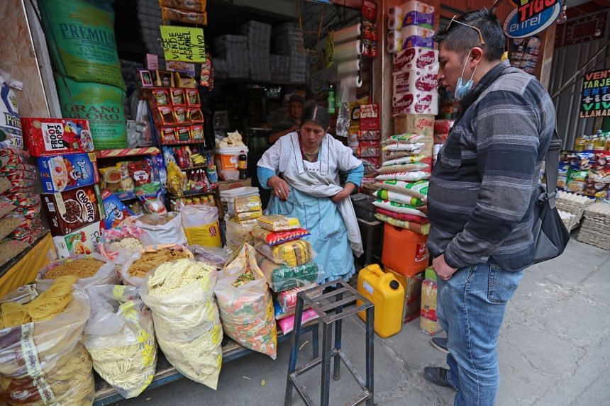 Bolivian citizens make purchases at a market in La Paz, March 20, 2020.