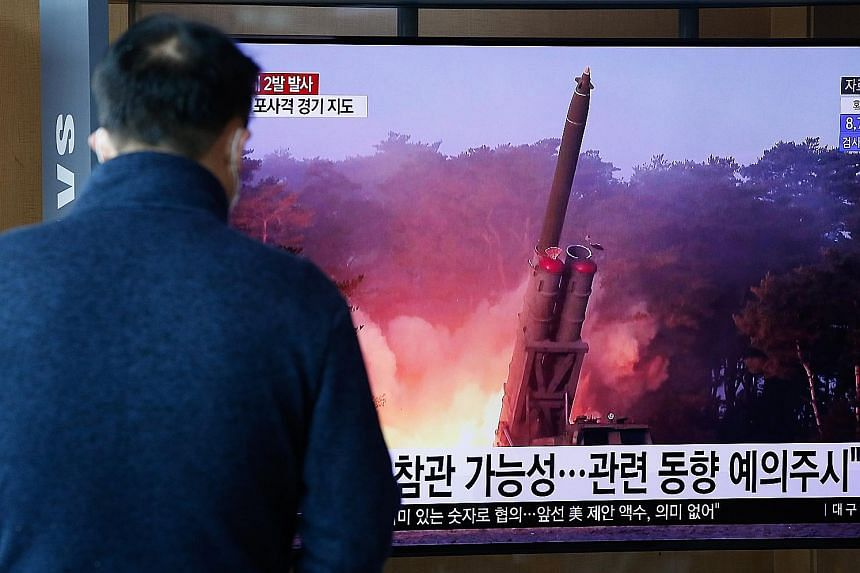 Above: A man in the South Korean capital Seoul watching breaking news of North Korea's projectile launch yesterday. Left: North Korea's leader Kim Jong Un watching an artillery fire contest with high-ranking military officers last Friday.