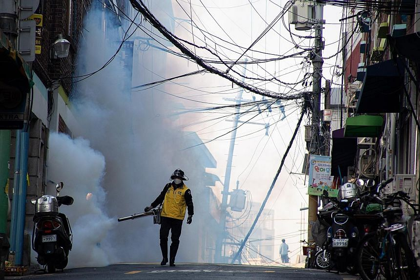 A worker spraying disinfectant as a precaution against further spread of the coronavirus in Seoul, South Korea, last Monday. Cluster infections account for 80 per cent of the country's confirmed cases, the largest cluster being linked to a branch of