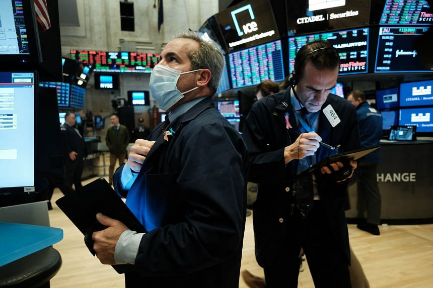 Traders, some in medical masks, work on the floor of the New York Stock Exchange in New York City, on March 20, 2020.