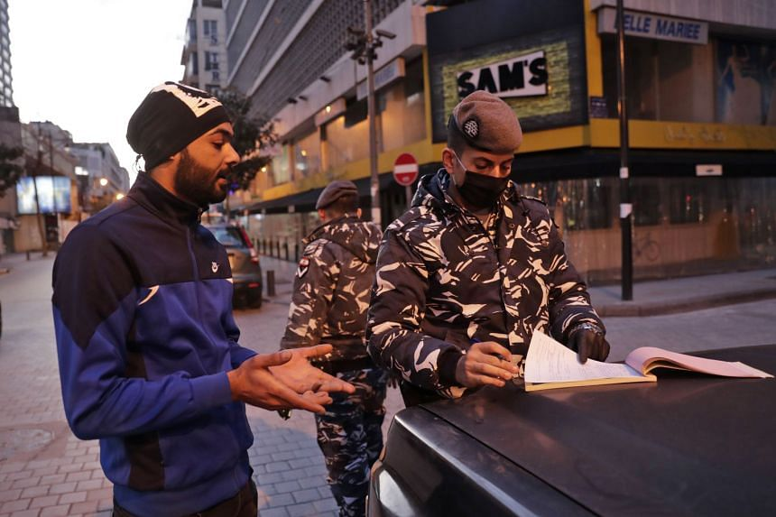 A man (left) is fined for violating lockdown rules in Beirut's Hamra street on March 21, 2020.