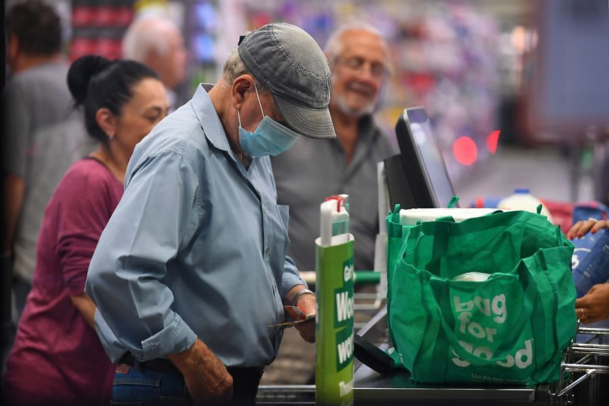 A man wears a face mask at a checkout in a Woolworths supermarket in Melbourne, Australia, on March 19, 2020.