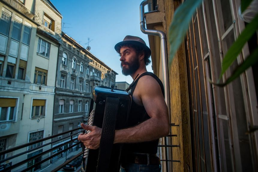 Hungarian musician and composer Adam Moser plays on an accordion on his balcony in Budapest, Hungary, on March 20, 2020.