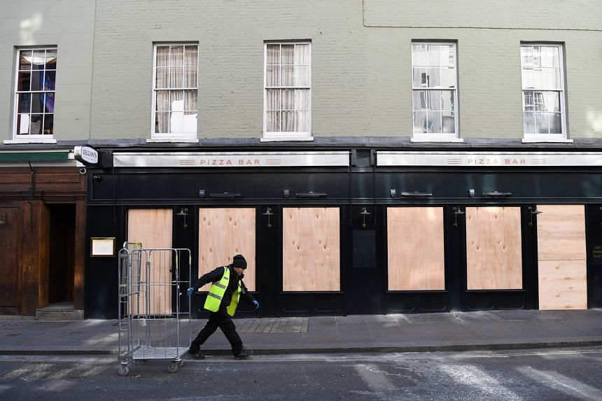 A worker walks past a boarded up pizza bar in Soho in London, Britain, on March 21, 2020.