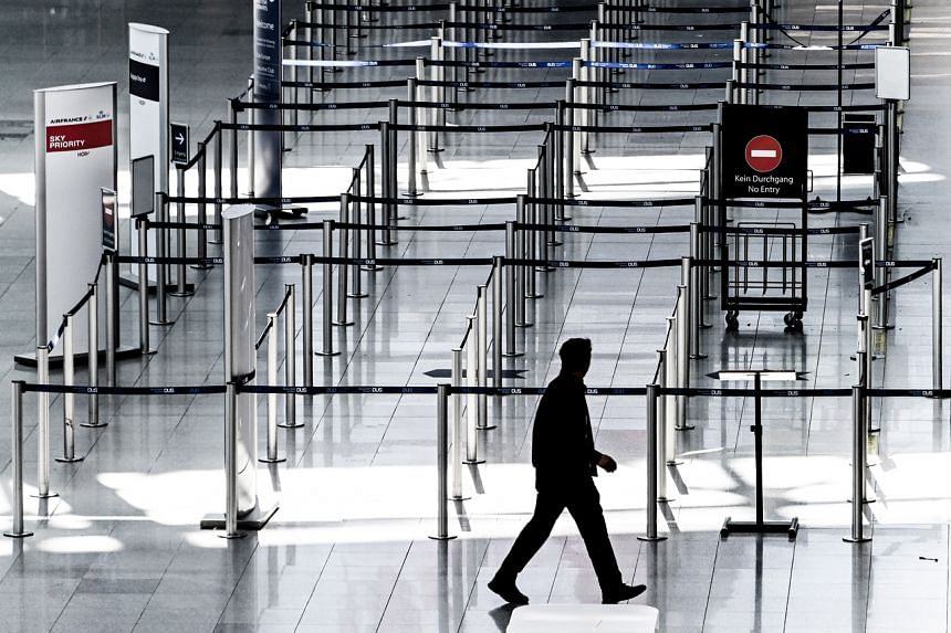 A man walks past the deserted check-in area of the international airport in Duesseldorf, Germany, on March 18, 2020.
