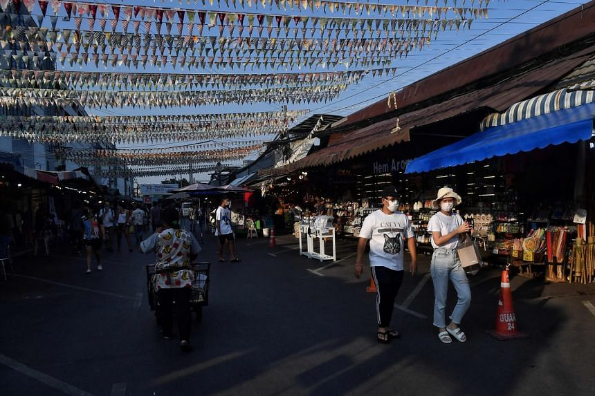 People in face masks walk through an unusually empty Chatuchak weekend market in Bangkok, on March 21, 2020.