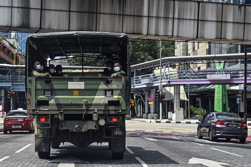 Soldiers wearing face masks look out from an army truck during the control of movement in Kuala Lumpur, on March 22, 2020.