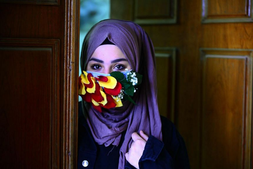 A woman is seen wearing a mask embellished with petals in the central Iraqi holy city of Najaf on March 21, 2020