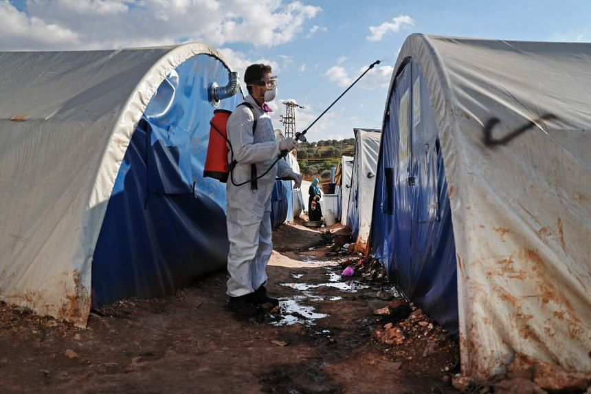 An NGO worker disinfects tents at a camp for displaced people in a village north of Idlib, Syria, on March 21, 2020  as a preventive measure against the spread of the coronavirus.