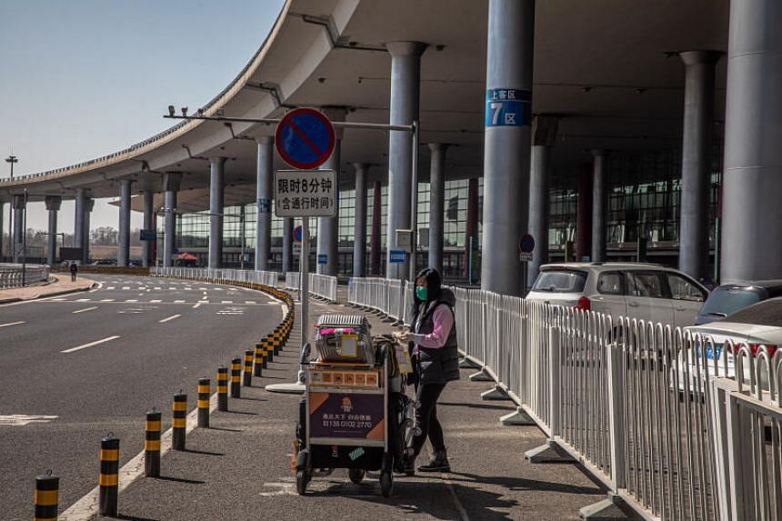 A photo taken on March 17, 2020 shows a traveller with a protective mask waiting with her lugage in an empty area outside the Capital International Airport in Beijing.