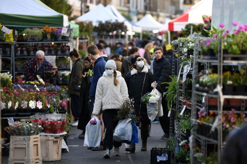 A photo taken on March 22, 2020 shows shoppers with protective face masks carry flowers after a visit to Columbia Road flower market in east London.
