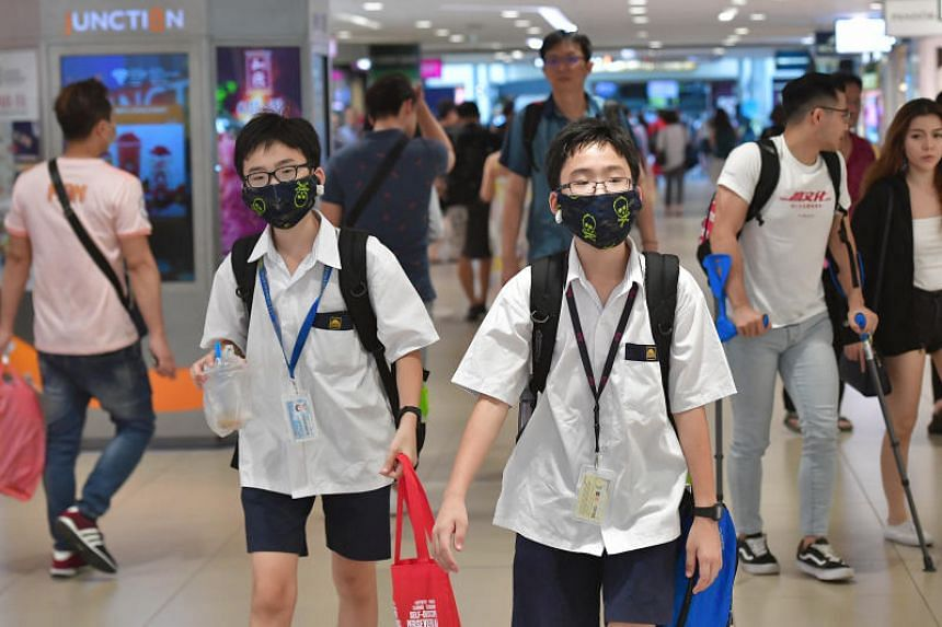 A photo taken on Feb 25, 2020 shows two school boys with masks at Junction 8. Education Minister Ong Ye Kung cited scientific evidence, extra precautions, and a desire to reduce disruptions as key considerations in allowing students to resume classes