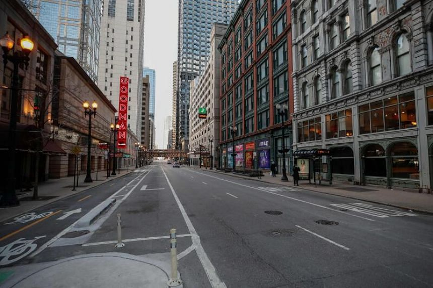 A woman waits for a bus on a nearly empty street in Chicago on March 21, 2020.