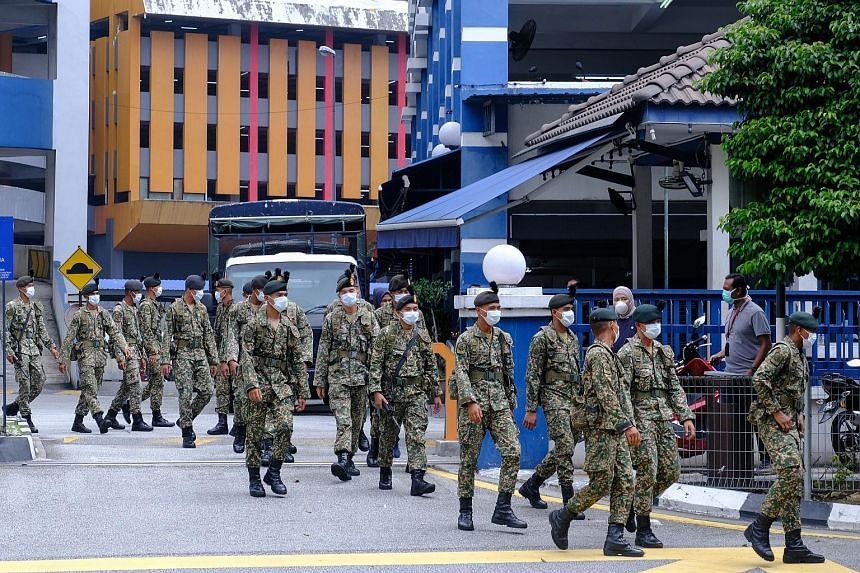 Army personnel leaving a police station in Kuala Lumpur yesterday. The uniformed personnel will be mobilised in cities and rural areas, including at borders, hospitals, supermarkets and wet markets, to ensure people obey the stay-home order.