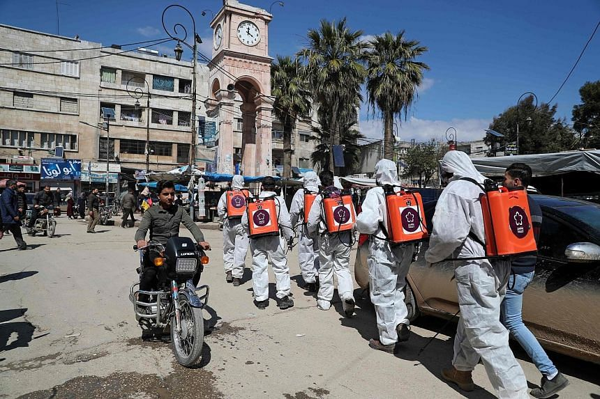 """Members of Syrian non-governmental organisation Violet disinfecting streets in north-western Idlib city last Saturday as a preventive measure against the spread of the coronavirus. Evoking the """"potentially devastating impact"""" of Covid-19 in Idlib and"""