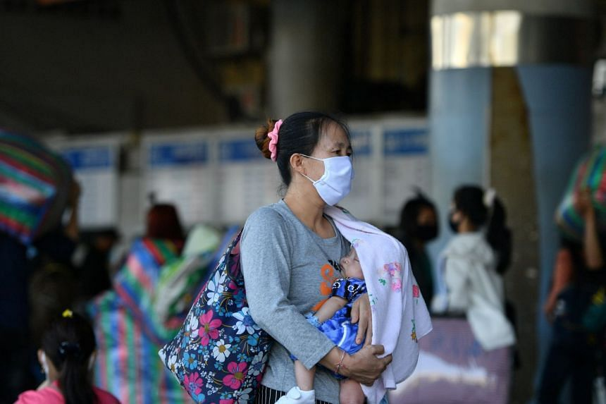 A woman wearing a mask carries a baby at a bus station in Bangkok on March 22, 2020.