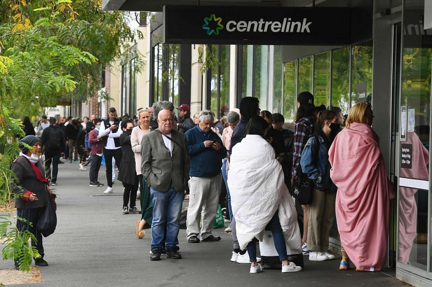 Hundreds of people queue outside an Australian government welfare centre, Centrelink, in Melbourne, Australia, on March 23, 2020.