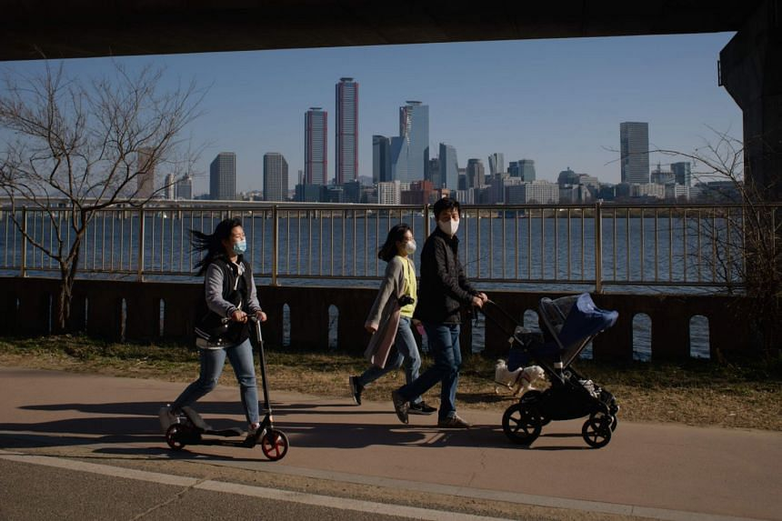 A family wearing face masks walk along the Han river in Seoul on March 22, 2020.