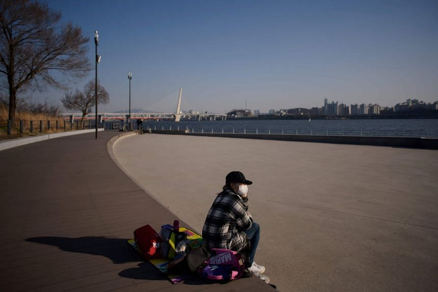 A woman wearing a face mask sits in South Korea on March 22, 2020.