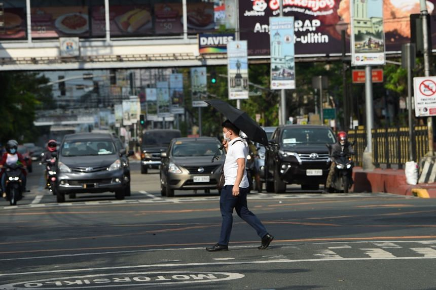 A pedestrian wearing a face mask crosses a road in Manila, Philippines on March 20, 2020.
