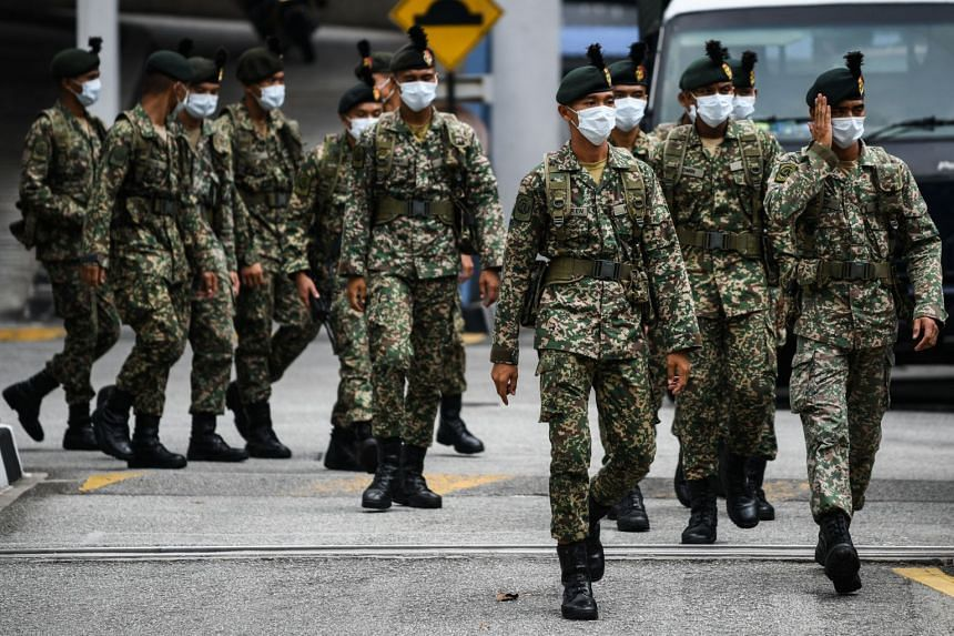 Soldiers leave a police station to man roadblocks during the control of movement in Kuala Lumpur, Malaysia, on March 22, 2020.