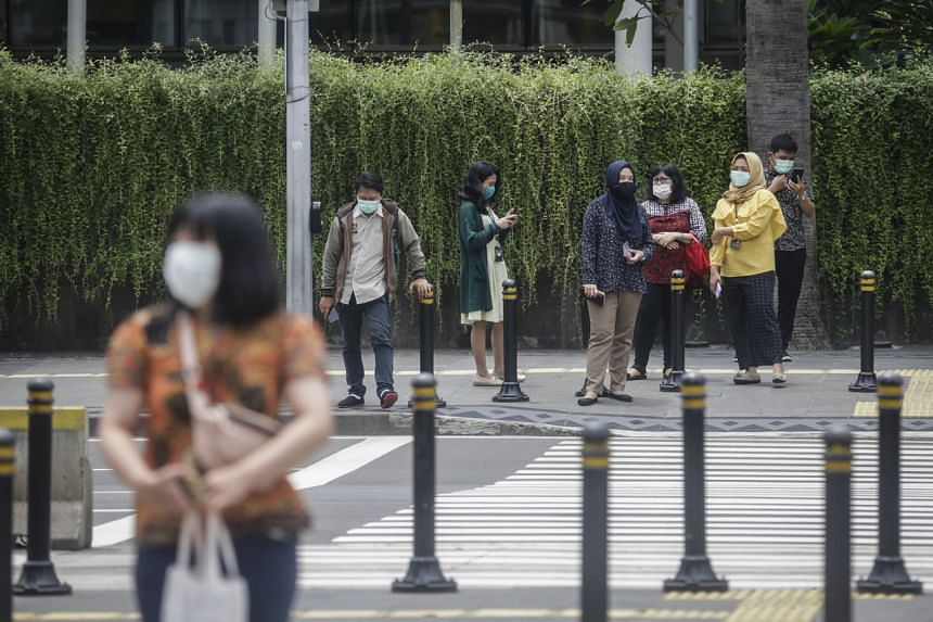 People with protective face masks waiting to cross a street in Jakarta on March 23, 2020.