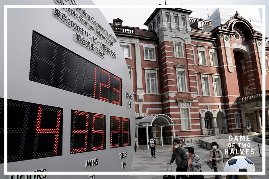 Pedestrians wearing masks walk past a countdown clock displaying the time until the opening of the Tokyo Olympic Games outside Tokyo railway station in Tokyo, Japan, 23 March 2020. Japanese Prime Minister Shinzo Abe said on 23 March 2020 that the pos
