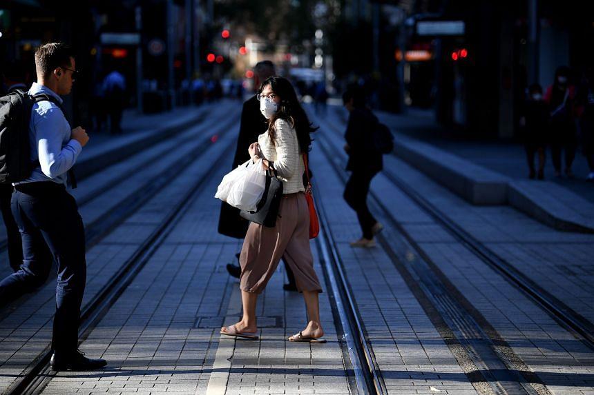 A woman wearing a face mask walks on a street in Sydney, Australia, on March 19, 2020.